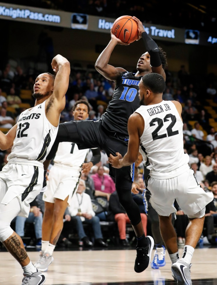 <strong>University of Memphis guard Damion Baugh (middle) is called for a charging foul while driving the lane against UCF defenders Dazon Ingram (left) and Darin Green Jr. (right) during action on Jan. 29, 2020, in Orlando.</strong> (Mark Weber/Daily Memphian)