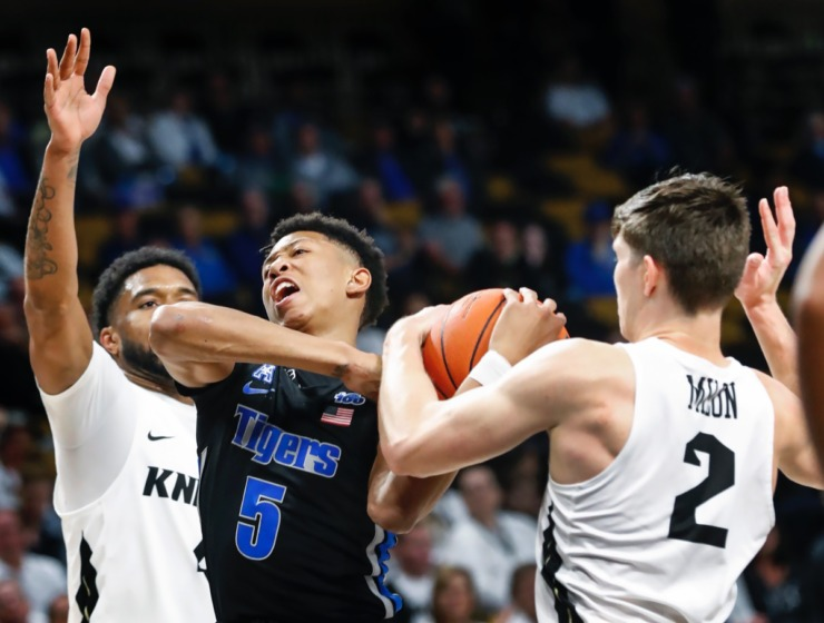 <strong>Memphis guard Boogie Ellis (middle) loses control of the ball while driving the lane against UCF defenders Ceasar DeJesus (left) and Matt Milon (right) during action on Wednesday, Jan. 29, 2020, in Orlando.</strong> (Mark Weber/Daily Memphian)
