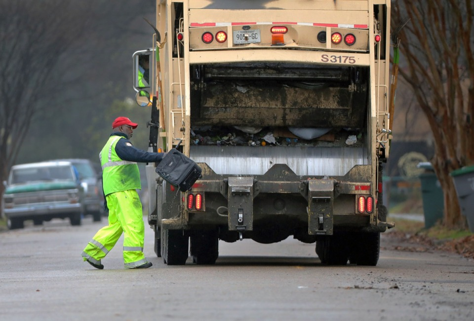 <strong>A sanitation worker tosses an old, water-logged suitcase into a garbage truck while making the rounds in the Evergreen neighborhood of Midtown Jan. 31, 2020.</strong>&nbsp;<strong>Some sanitation workers are upset over compulsory overtime to clear a backlog of leaf pickups.</strong>&nbsp;(Patrick Lantrip/Daily Memphian)