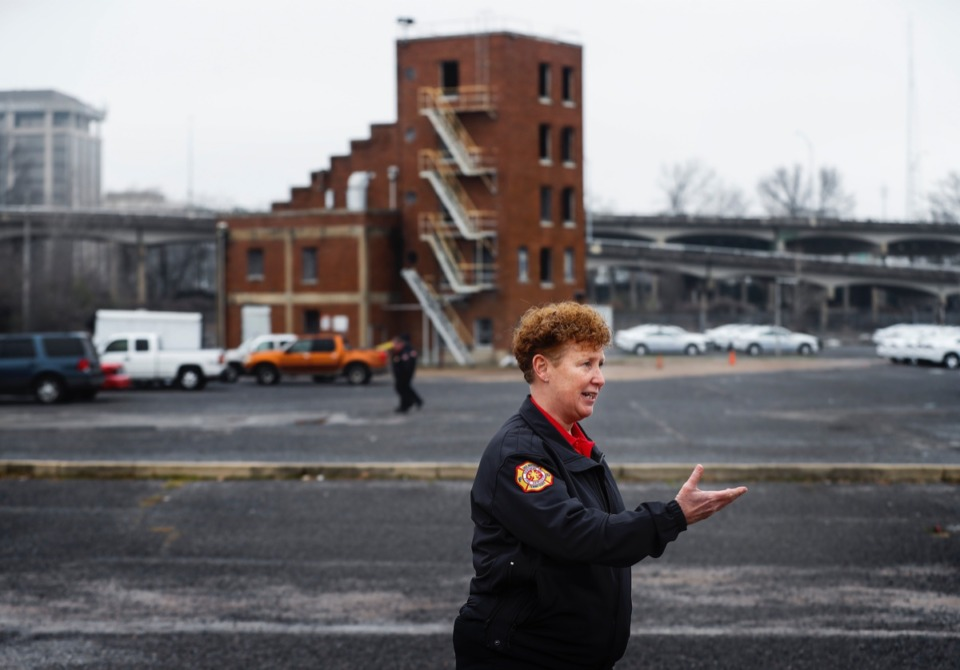 <strong>Memphis Fire Director Gina Sweat gestures Friday, Jan. 31, 2020, toward the area where a new department headquarters will be built on Avery Avenue. The old drill tower (background) will stay with the hopes of turning it into a wellness center.</strong> (Mark Weber/Daily Memphian)