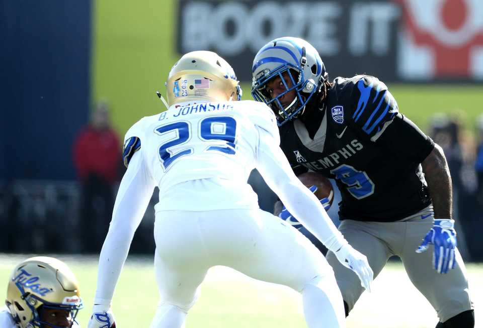 "<strong>Memphis Tigers' John ""Pop"" Williams (9) jukes Tulsa safety Brandon Johnson (29) as he tries to gain yards in the game on Saturday, Nov. 10, 2018.</strong> (Houston Cofield/Daily Memphian)"