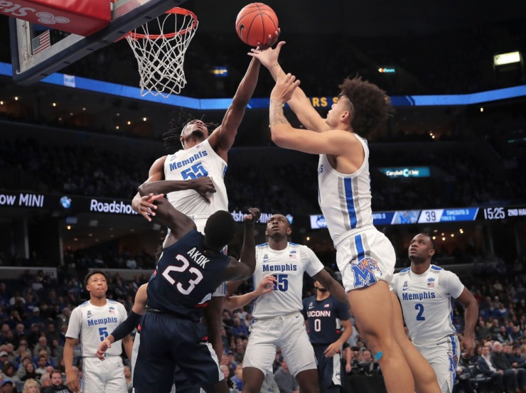 <strong>University of Memphis forward Precious Achiuwa (55) and guard Lester Quinones pull down a rebound under pressure by the Huskies' Akok Akok (23) during the Tigers' game on Feb. 1, 2020, against Connecticut at FedExForum in Memphis.</strong> (Jim Weber/Daily Memphian)