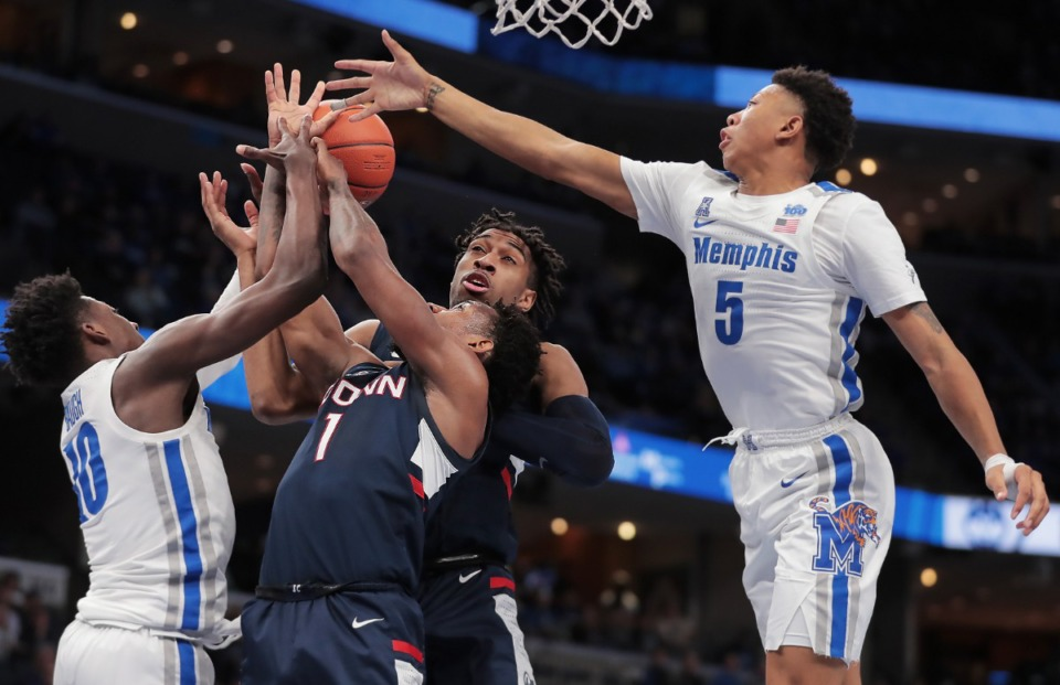 <strong>University of Memphis guards Damion Baugh (left) and Boogie Ellis (5) battle for a rebound with the Huskies' Christian Vital (1) and Isaiah Whaley during the Tigers' game on Feb. 1 2020, against Connecticut at the FedExForum</strong>.(Jim Weber/Daily Memphian)