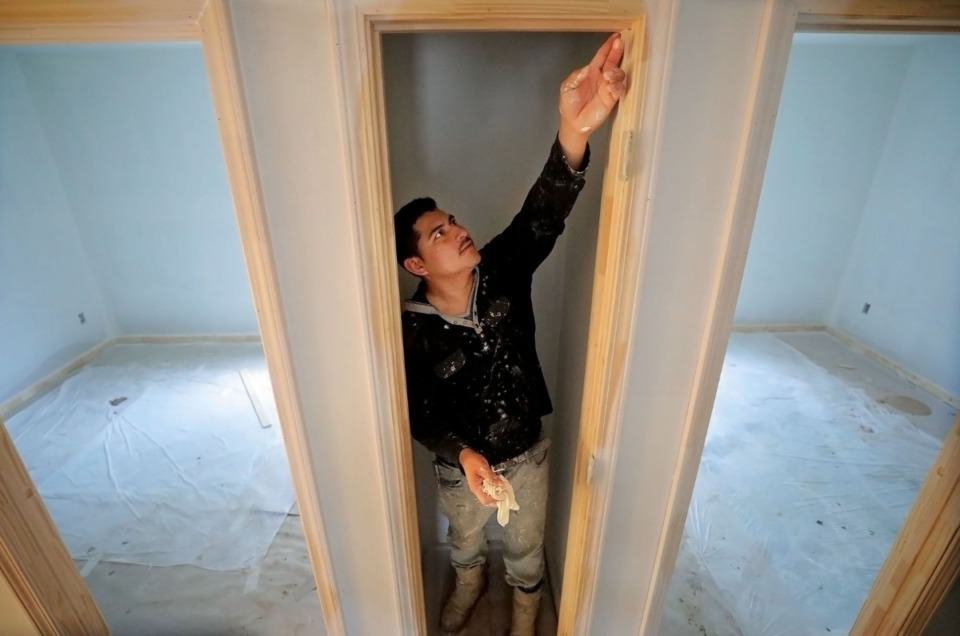 <strong>Marcos Garcia seals a door frame with silicone caulk while renovating a home in Frayser Feb. 4, 2020. Recently the North Memphis neighborhood has seen a significant uptick in housing activity.</strong> (Patrick Lantrip/Daily Memphian)