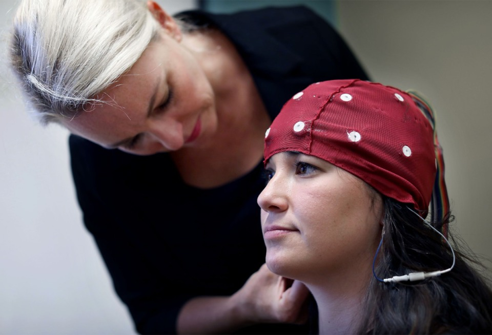 <strong>Dr. Eraina Schauss places a cap on the head of Paige Dixon to perform a qEEG (quantitative electroencephalograph), which maps the neural pathways in the human brain.</strong> (Patrick Lantrip/Daily Memphian file)