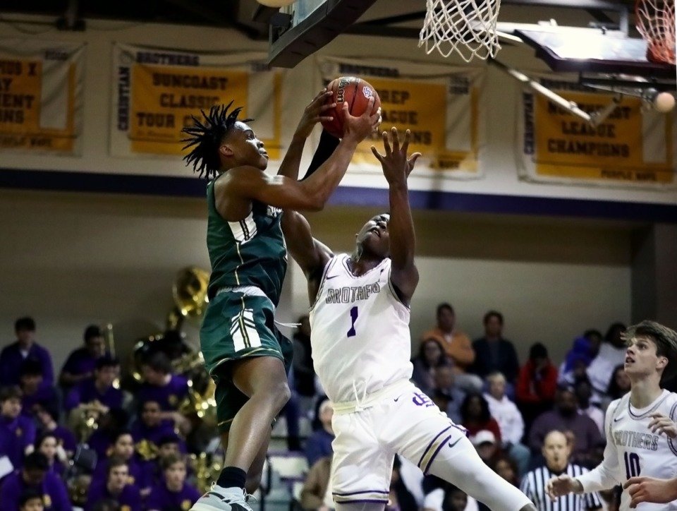 <strong>Briarcrest guard Marcellus Brigham (4) fights for a rebound with a CBHS guard during a road victory over rival CBHS Feb. 7, 2020.</strong> (Patrick Lantrip/Daily Memphian)