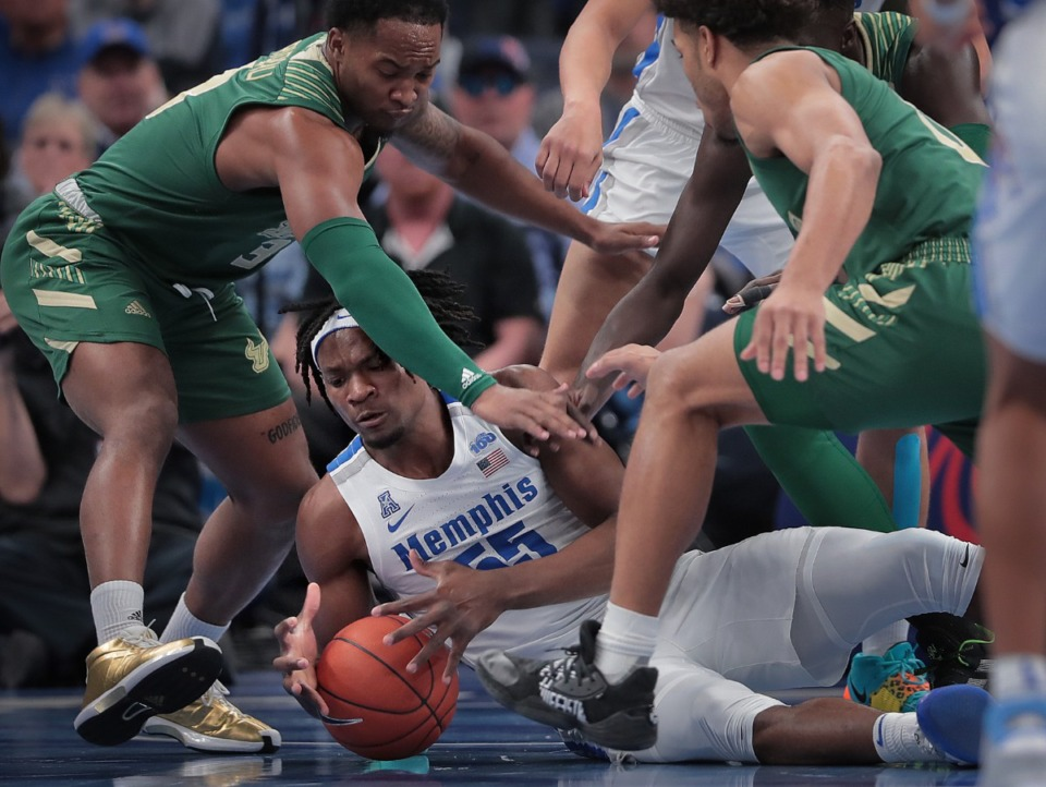 """<strong>University of Memphis forward Precious Achiuwa (55) scrambles for a loose ball under pressure from the Bulls' Laquincy Rideau (left) and Xavier Castaneda (right) during the Tigers' game on Feb. 8, 2020,&nbsp;<span class=""""s1"""">against the University of South Florida at FedExForum in Memphis</span>. </strong>(Jim Weber/Daily Memphian)"""