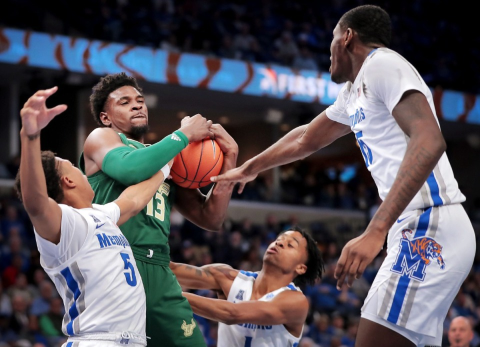 <strong>Bulls forward Justin Brown pulls down a rebound under pressure by University of Memphis guard Boogie Ellis (5), Tyler Harris (center) and Lance Thomas (right) during the Tigers' game on Feb. 8, 2020, against USF at FedExForum in Memphis.</strong> (Jim Weber/Daily Memphian)