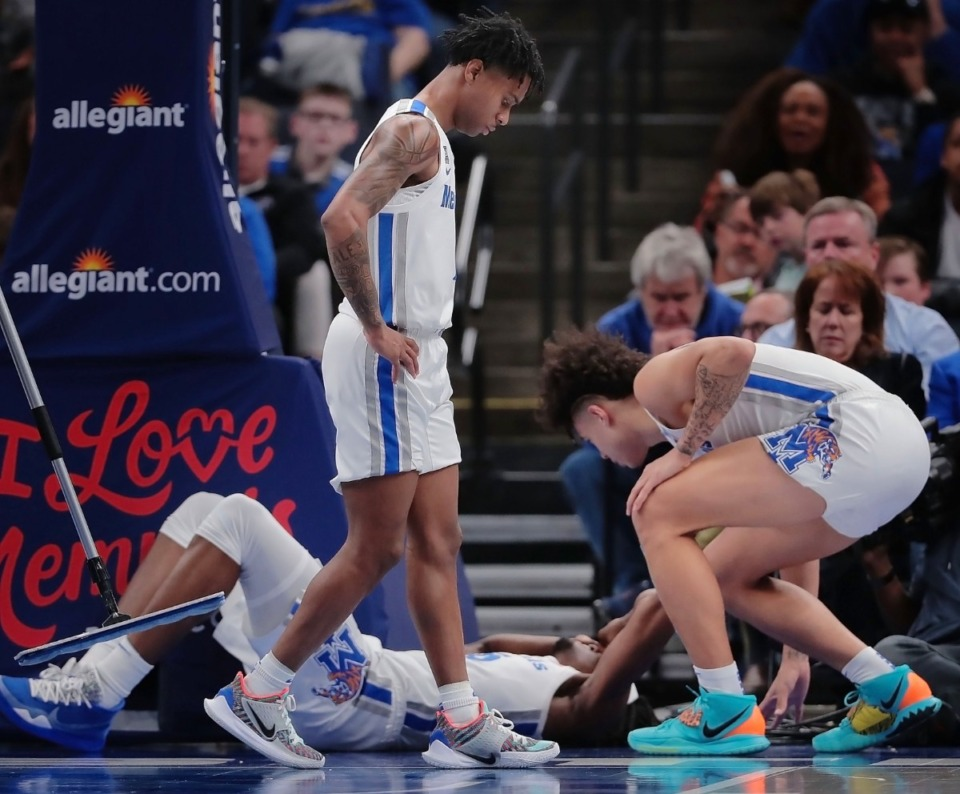 <strong>University of Memphis guard Lester Quinones (right) checks on Precious Achiuwa after he was injured during the Tigers' game on Feb. 8, 2020, against USF at the FedExForum in Memphis, TN.</strong> (Jim Weber/Daily Memphian)