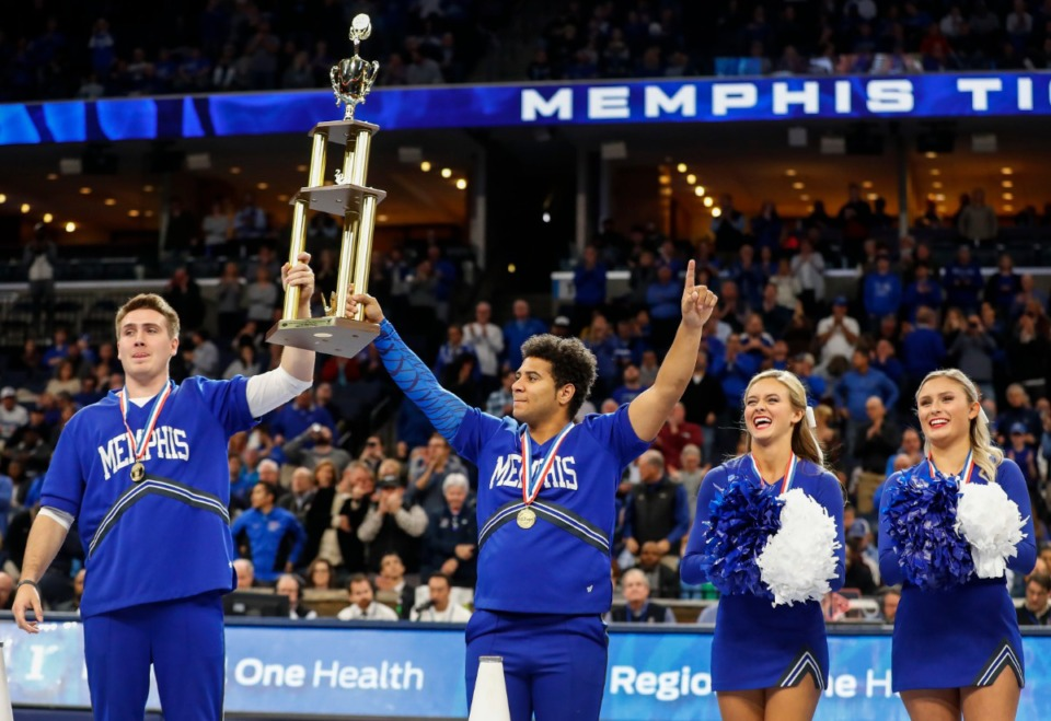 <strong>Members of the University of Memphis cheerleading squad celebrate with their national championship trophy during a break in action against Temple on Feb. 5, 2020 at FedExForum.</strong> (Mark Weber/Daily Memphian)