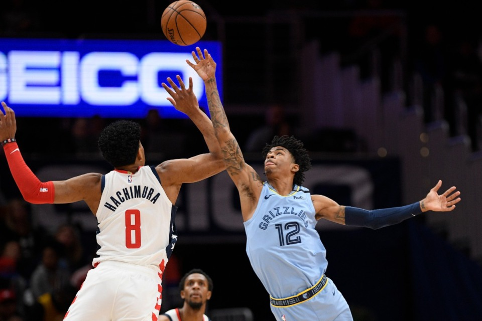 <strong>Memphis Grizzlies guard Ja Morant (12) and Washington Wizards forward Rui Hachimura (8) battle for the ball during the first half of an NBA game on Feb. 9, 2020, in Washington.</strong> (AP Photo/Nick Wass)