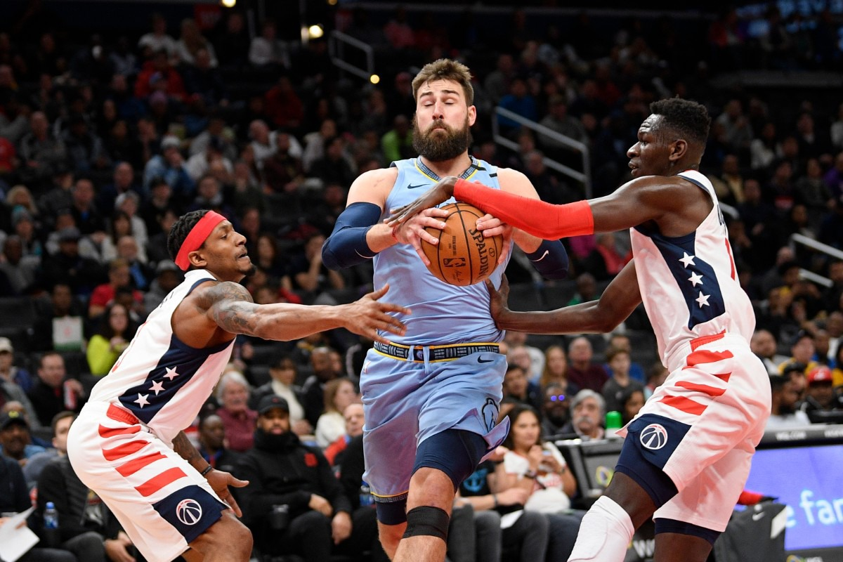 <strong>Washington Wizards guard Bradley Beal (left) fouls Memphis Grizzlies center Jonas Valanciunas, center, during the first half of an NBA game on Feb. 9, 2020, in Washington. Wizards forward Isaac Bonga (right) defends.</strong> (AP Photo/Nick Wass)