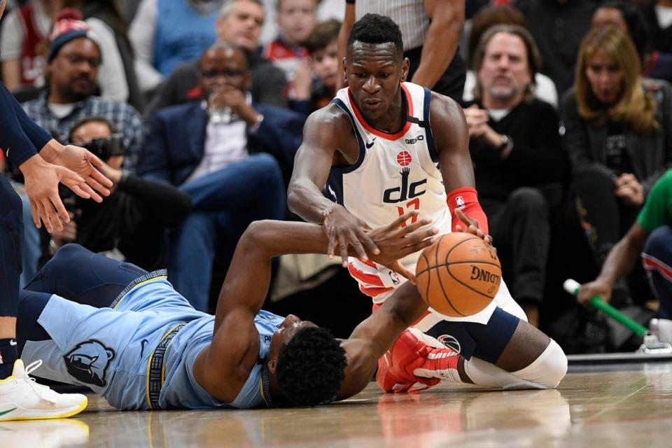 <strong>Washington Wizards forward Isaac Bonga (17) and Memphis Grizzlies forward Jaren Jackson Jr. (bottom) battle for the ball during the first half of an NBA game on Feb. 9, 2020, in Washington.</strong> (AP Photo/Nick Wass)
