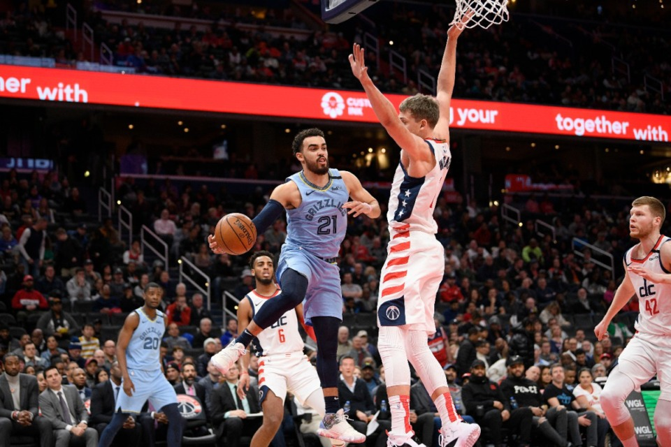 <strong>Memphis Grizzlies guard Tyus Jones (21) looks to pass next to Washington Wizards forward Moritz Wagner (center right) during the first half of an NBA game on Feb. 9, 2020, in Washington.</strong> (AP Photo/Nick Wass)