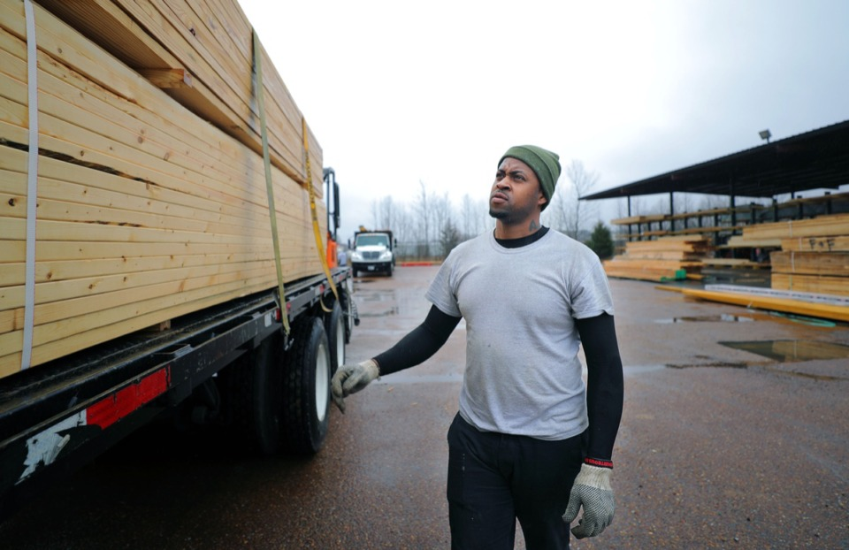 <strong>Sunrise Builders Supply driver Akeem Morman pays close attention as he tightens up the straps holding his load of lumber in place before hitting the road for a delivery Feb. 10, 2020. Sunrise Builders Supply has added a second location in Arlington with the hopes of capitalizing on future development in the area.</strong> (Patrick Lantrip/Daily Memphian)