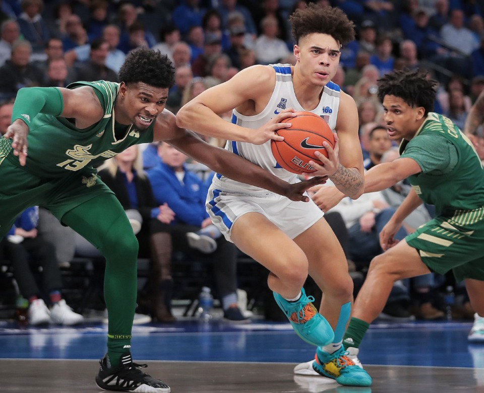 <strong>University of Memphis guard Lester Quinones finds an opening between the Bulls' Justin Brown (13) and Xavier Castaneda (right) Feb. 8, 2020, against USF at FedExForum. The Tigers lost, 79-72.</strong> (Jim Weber/Daily Memphian)