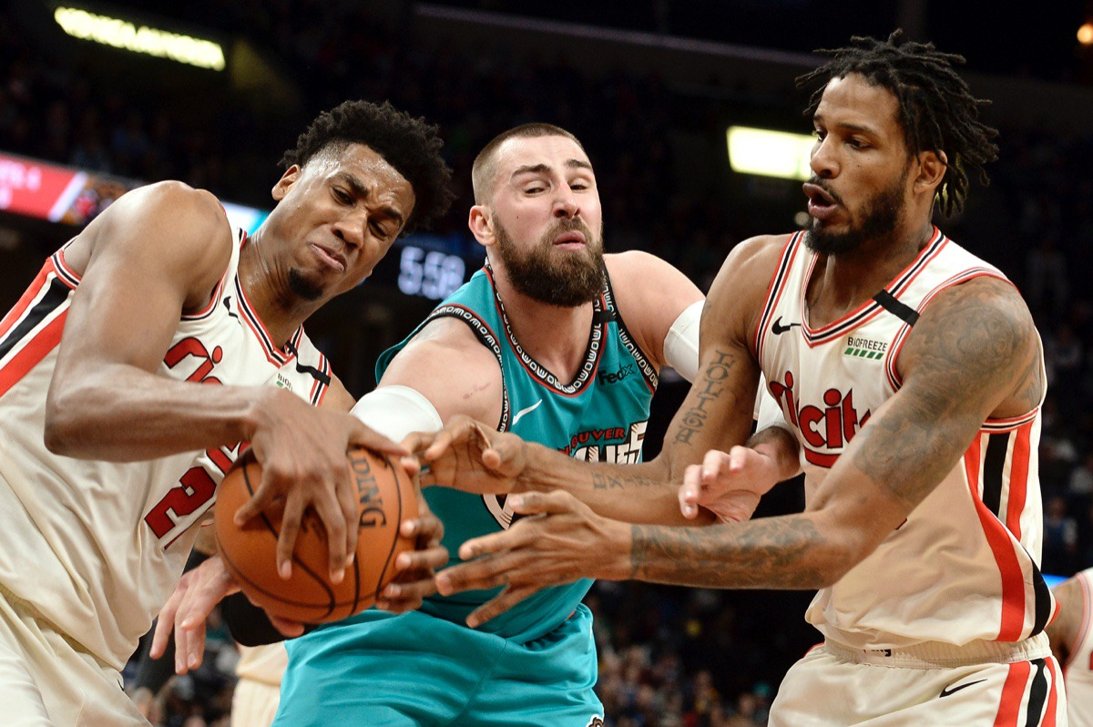 <strong>Portland Trail Blazers center Hassan Whiteside, left, Memphis Grizzlies center Jonas Valanciunas and Trail Blazers forward Trevor Ariza struggle for control of the ball&nbsp;Feb. 12, 2020, at FedExForum.</strong> (Brandon Dill/AP)