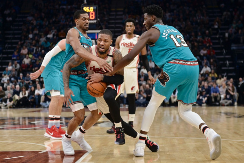 <strong>Portland Trail Blazers guard Damian Lillard (0) drives between Memphis Grizzlies guard Josh Jackson, left, and forward Jaren Jackson Jr. (13)&nbsp;Feb. 12, 2020, at FedExForum.</strong> (Brandon Dill/AP)
