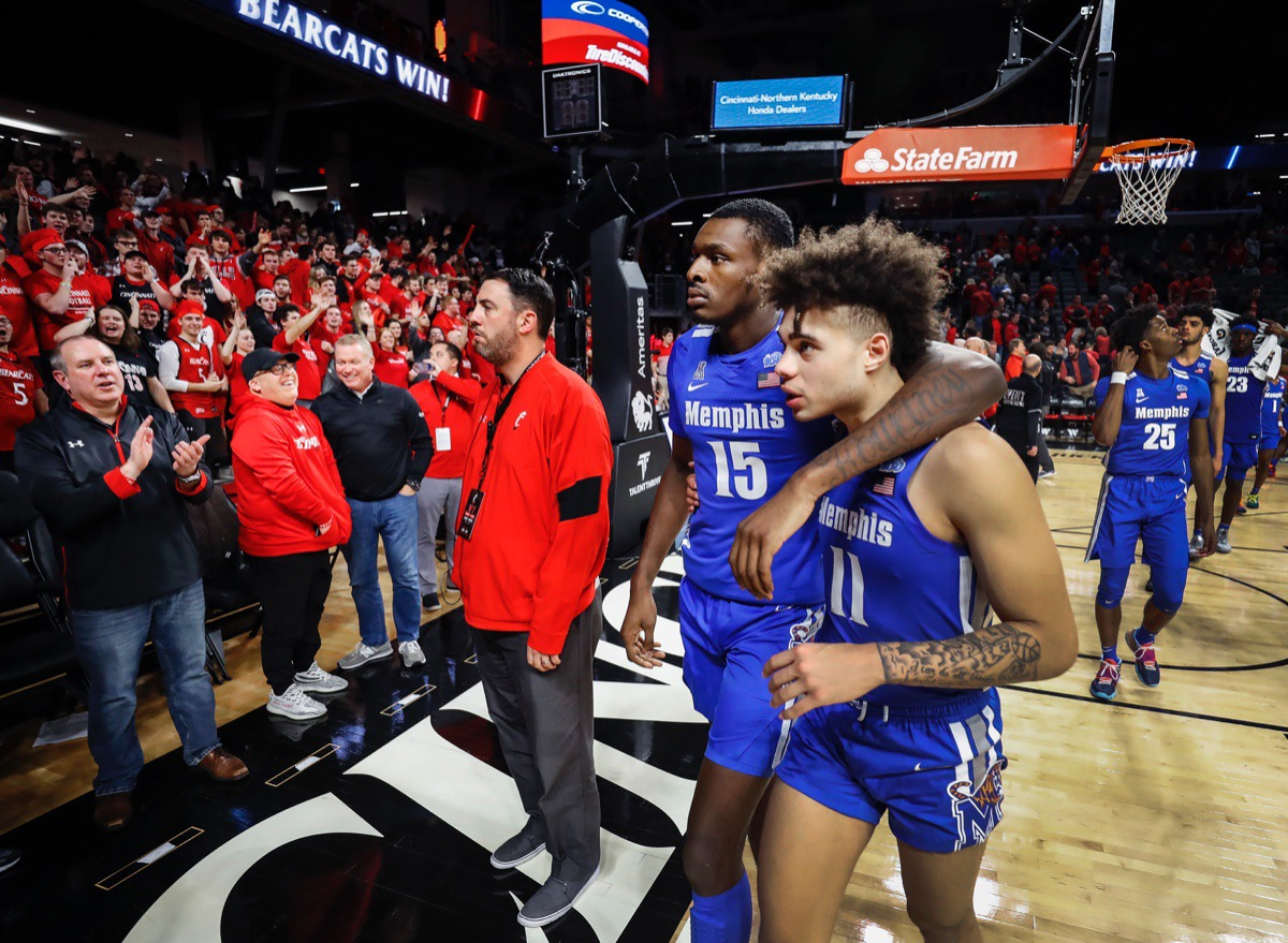 <strong>Memphis teammates Lance Thomas (middle) and Lester Quinones (right) walk off the court as the Cincinnati fans cheer after the Tigers lost 92-86 in overtime Thursday, Feb. 13, 2020.</strong> (Mark Weber/Daily Memphian)