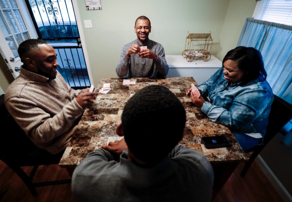 <strong>Pastor Charlie Caswell (middle) plays cards with Tuterrance Toney (left), his wife Melvia (right) and their son Cameron Brooks (bottom), Thursday, Feb. 6, 2020.&nbsp;Caswell is leading the effort around addressing Adverse Childhood Experiences in Frayser through his nonprofit Legacy of Legends.&nbsp;</strong>(Mark Weber/Daily Memphian)