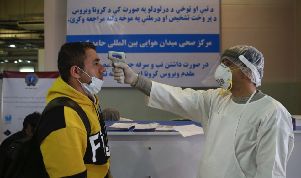 <strong>An Afghan health worker takes the temperature of a passenger as preventive measures for Coronavirus, during a screening process of travelers who arrived from China, at the Hamid Karzai International Airport in Kabul, Afghanistan, Feb. 3, 2020.</strong>&nbsp;<strong>More than 1,300 have died from the virus already.</strong> (Rahmat Gul/AP)