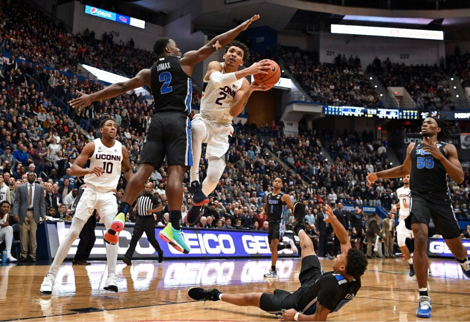 <strong>Connecticut's James Bouknight (2) is fouled by Memphis' Alex Lomax (2) as he goes up for a basket during a game on Feb. 16, 2020, in Hartford, Conn.</strong> (AP Photo/Jessica Hill)