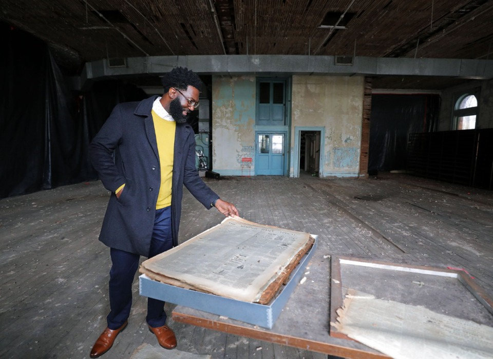 <strong>Shamichael Hallman, a former minister who is now heading the project to reimagine the Cossitt Library, looks at a 144-year-old old edition of the Memphis Daily Appeal that was found sealed inside the original half of the city's oldest library on Jan. 16, 2020.</strong> (Patrick Lantrip/Daily Memphian)