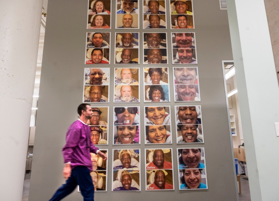 "<strong>Dentist Steven Oxner walks past the ""wall of smiles"" at the Church Health dental clinic on Feb. 19, 2020, at Crosstown Concourse. Patients who have had major dental work at the clinic have their ""before"" and ""after"" photos displayed on the wall in the clinic.</strong> (Greg Campbell/Special to The Daily Memphian)"