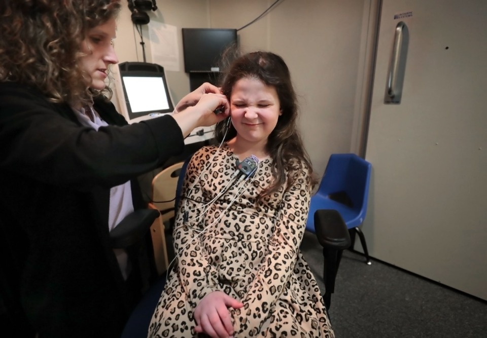 <strong>Eight-year-old Gigi Benassi winces as a pressure probe tickles her ear during a comprehensive hearing test with Audiologist Rachel Lunsford at the Memphis Oral School for the Deaf on Jan. 30, 2020. Gigi is moderately to severely deaf.</strong> (Jim Weber/Daily Memphian)