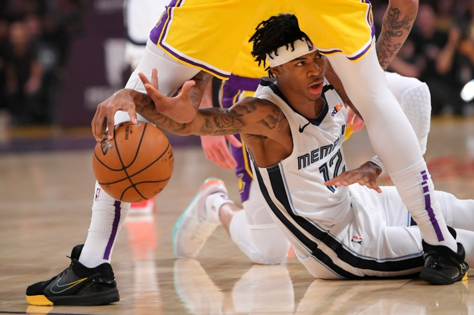 <strong>Memphis Grizzlies guard Ja Morant, below, tries to pass the ball from under the legs of Los Angeles Lakers forward Anthony Davis during the first half of an NBA basketball game Friday, Feb. 21, 2020, in Los Angeles.</strong> (Mark J. Terrill/AP)