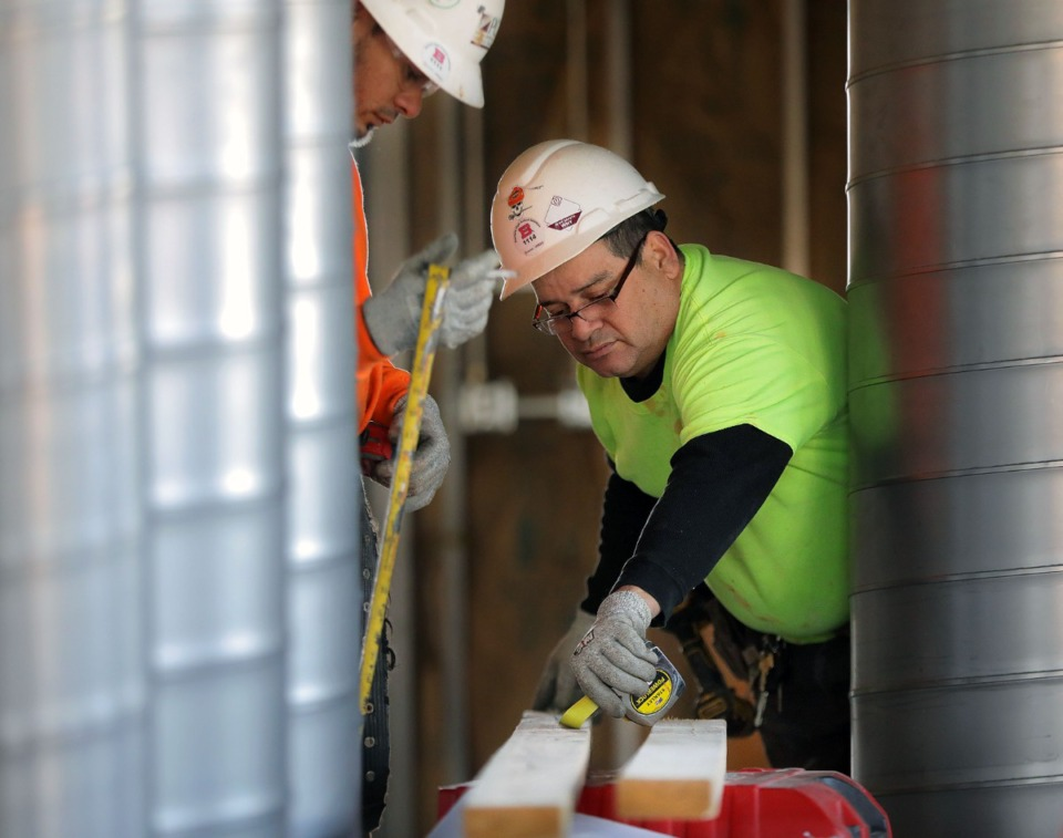 <strong>Eyerbin Oritz (right) and Marco Jui (left) measure a wooden stud Feb. 19, 2020 while working on the interior buildout of a new independent neighborhood pharmacy known as the Arlington Apothecary, a first for the northeast Shelby County suburb.</strong> (Patrick Lantrip/Daily Memphian)