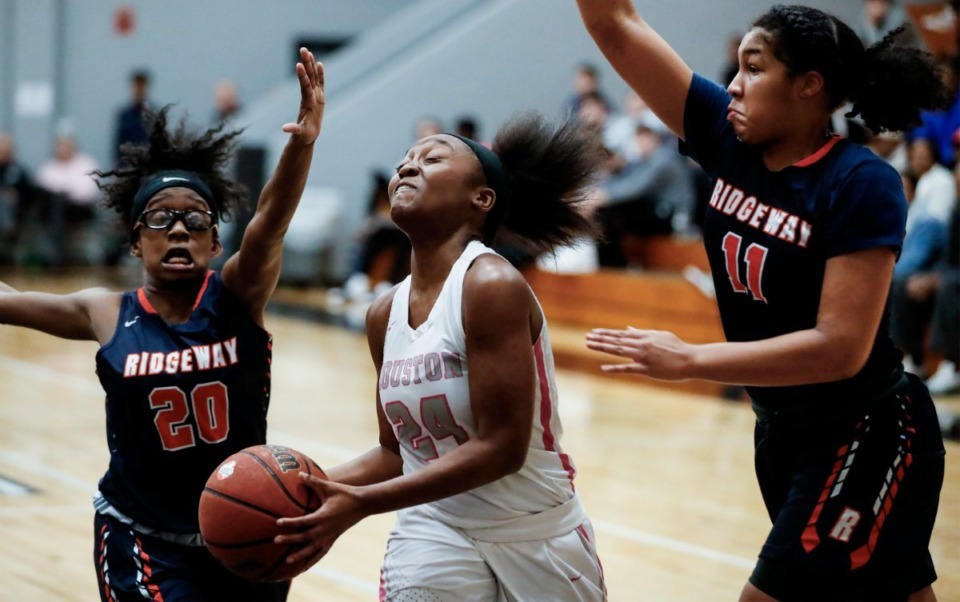 <strong>Houston guard Destinee Wells (middle) drives for a layup against Ridgeway defenders Andrea Lee (left) and Amaya Mull (right) during action on Tuesday, Feb. 25, 2020 in Germantown.</strong> (Mark Weber/Daily Memphian)