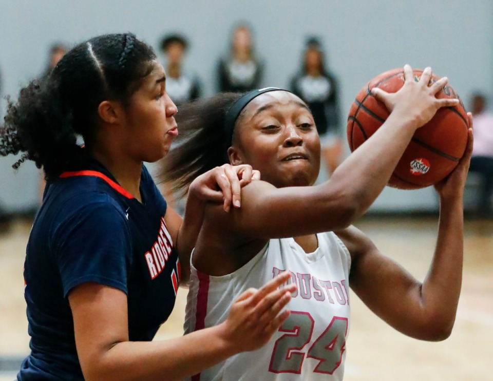 <strong>Houston guard Destinee Wells (middle) drives for a layup against Ridgeway defender Amaya Mull (left) during action on Tuesday, Feb. 25, 2020 in Germantown.</strong> (Mark Weber/Daily Memphian)