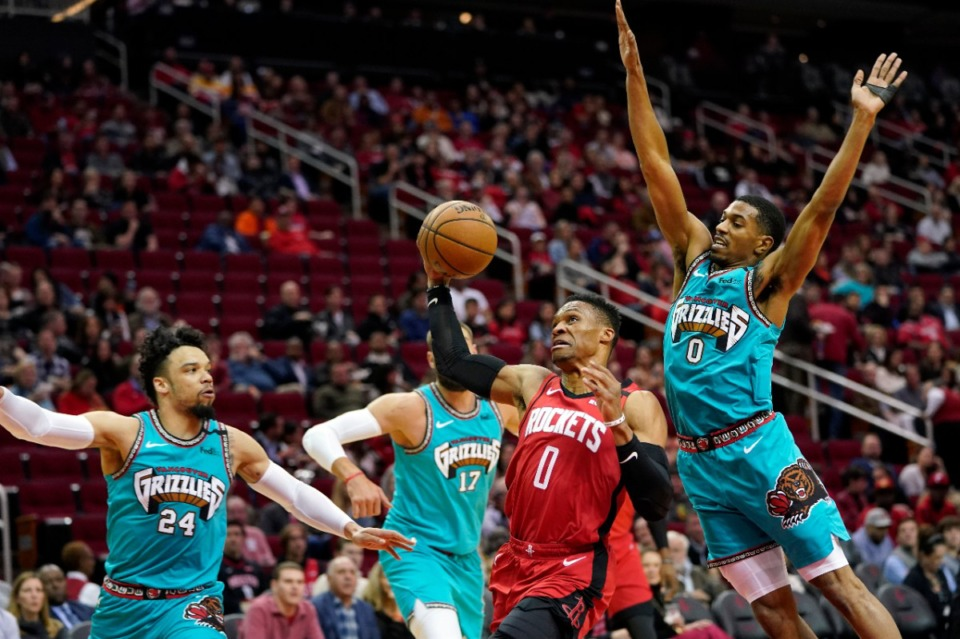 <strong>Houston Rockets' Russell Westbrook, center, goes up for a shot as Memphis Grizzlies' De'Anthony Melton, right, defends during the first half of an NBA basketball game Wednesday, Feb. 26, 2020, in Houston.</strong> (AP Photo/David J. Phillip)