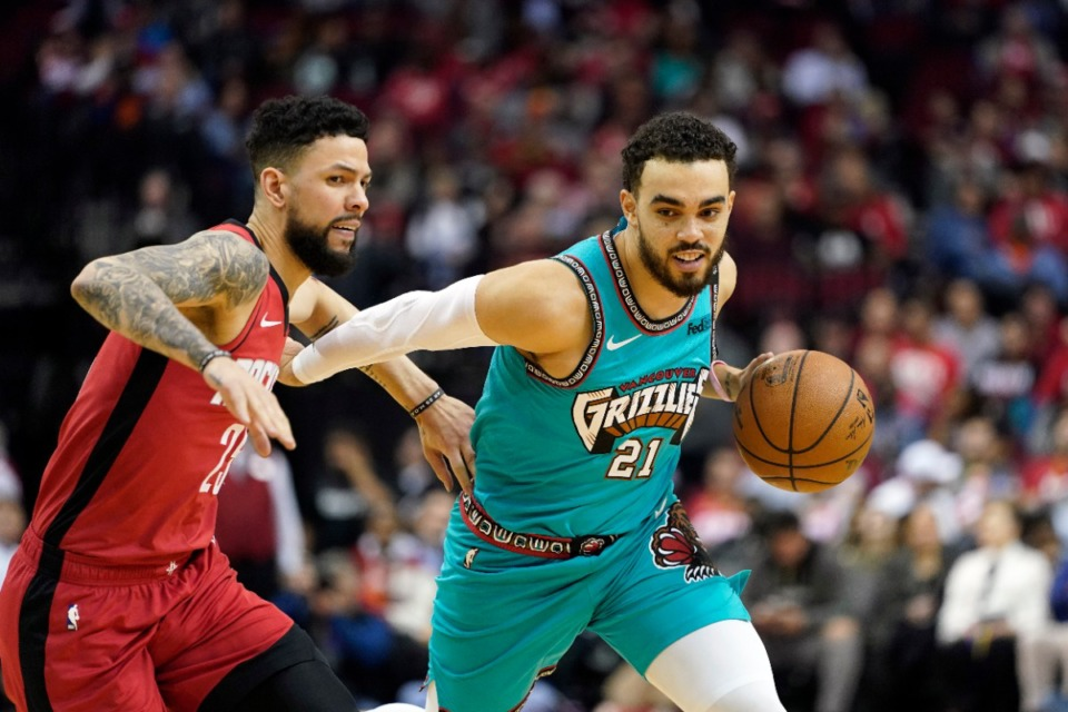 <strong>Memphis Grizzlies' Tyus Jones (21) drives toward the basket as Houston Rockets' Austin Rivers defends during the second half of an NBA basketball game Wednesday, Feb. 26, 2020, in Houston. The Rockets won 140-112.</strong> (AP Photo/David J. Phillip)