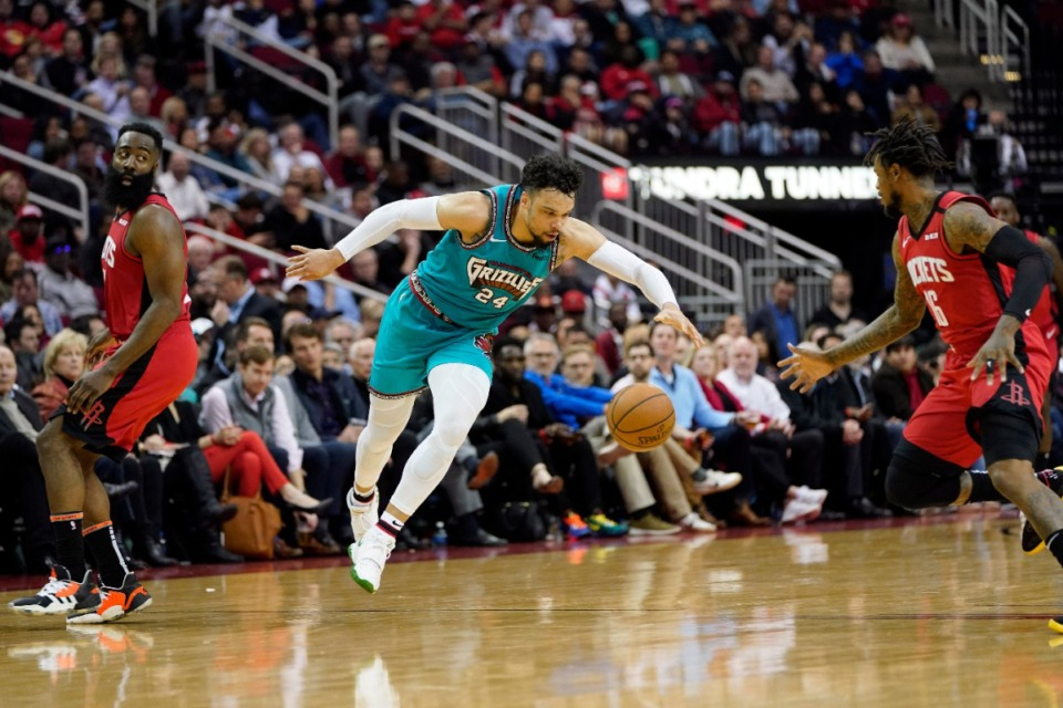 <strong>Memphis Grizzlies' Dillon Brooks (24) reaches for a loose ball between Houston Rockets' Ben McLemore (16) and James Harden during the second half of an NBA basketball game Wednesday, Feb. 26, 2020, in Houston. The Rockets won 140-112.</strong> (AP Photo/David J. Phillip)