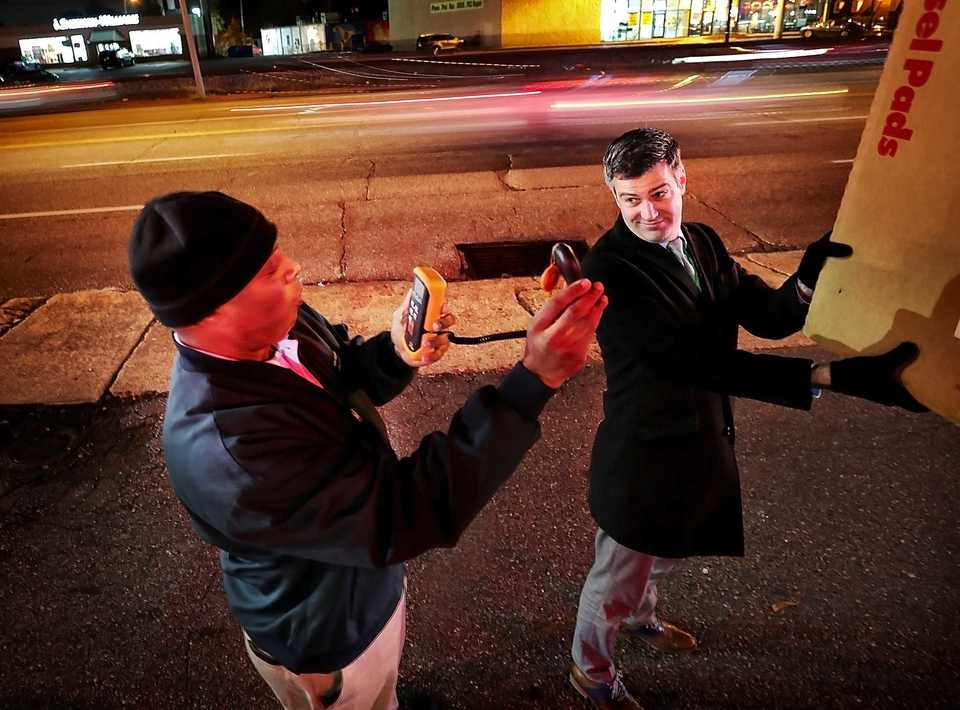 <strong>Memphis and Shelby County Planning Director Josh Whitehead (right) and senior zoning inspector Christopher Simmons use a light meter to measure the brightness of signs on Poplar Avenue on Nov. 13. Local code officers have a new tool to combat light pollution as they crack down on distracting signs in the Memphis area.</strong> (Jim Weber/Daily Memphian)