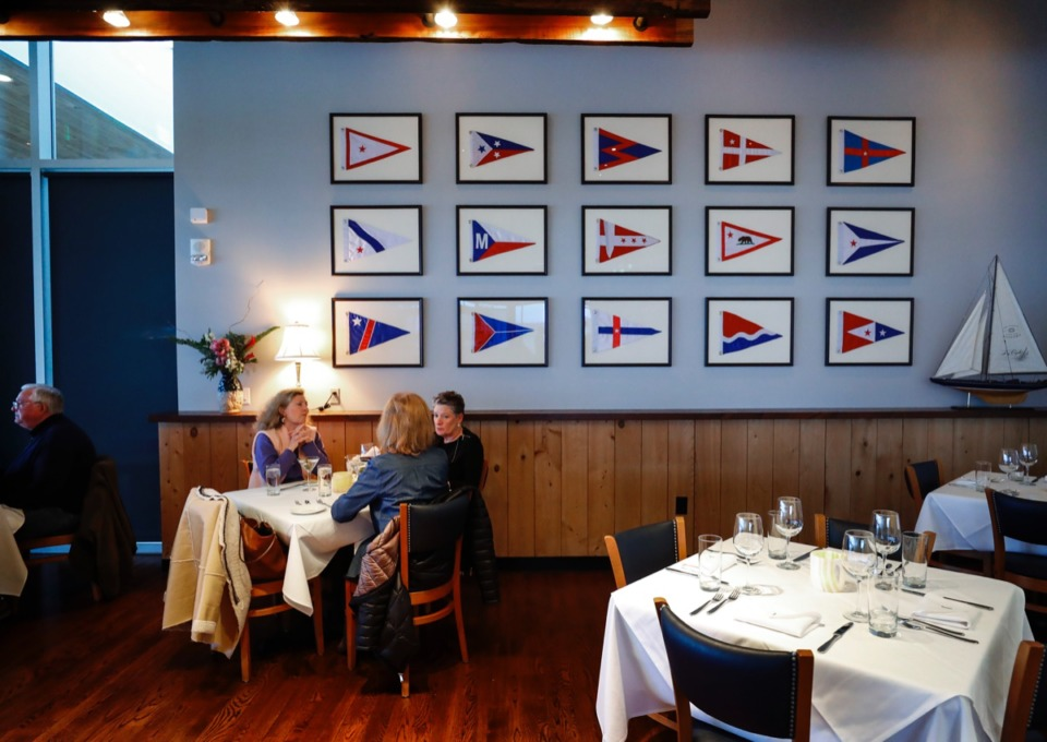 <strong>Coastal Fish Company customers enjoy themselves in a side room decorated with maritime flags on Wednesday, Feb. 26, 2020.</strong> (Mark Weber/Daily Memphian)