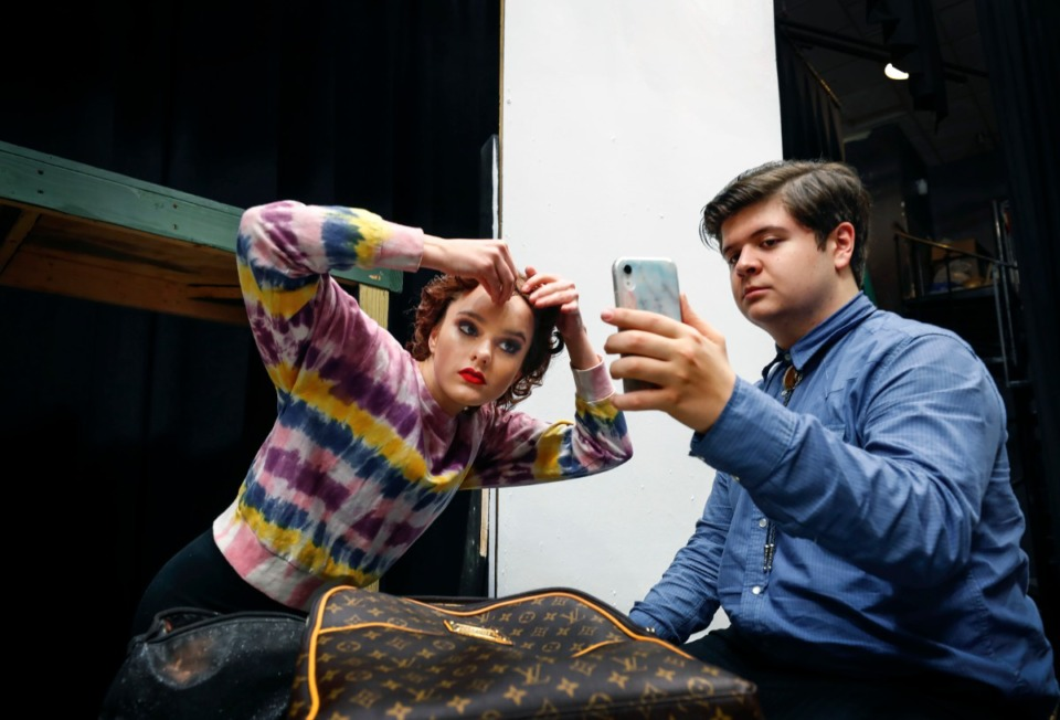 """<strong>Christian Brothers High School student Gabe McCarthy (right), who plays Carl Perkins, uses a smartphone as a mirror while home-school student Vivie Myrick, playing Dyanne, Elvis' girlfriend, fixes her wig before rehearsal of """"Million Dollar Quartet"""" on Feb. 18, 2020.</strong> (Mark Weber/Daily Memphian)"""