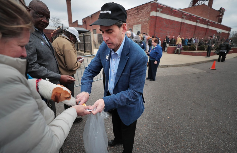<strong>Scot Lansky with the Bloomberg campaign passes out buttons to supporters like Robin Ross and her dog Ace at Minglewood Hall as Democratic presidential contender Michael Bloomberg makes a campaign stop in Memphis on Feb. 28, 2020.</strong> (Jim Weber/Daily Memphian)