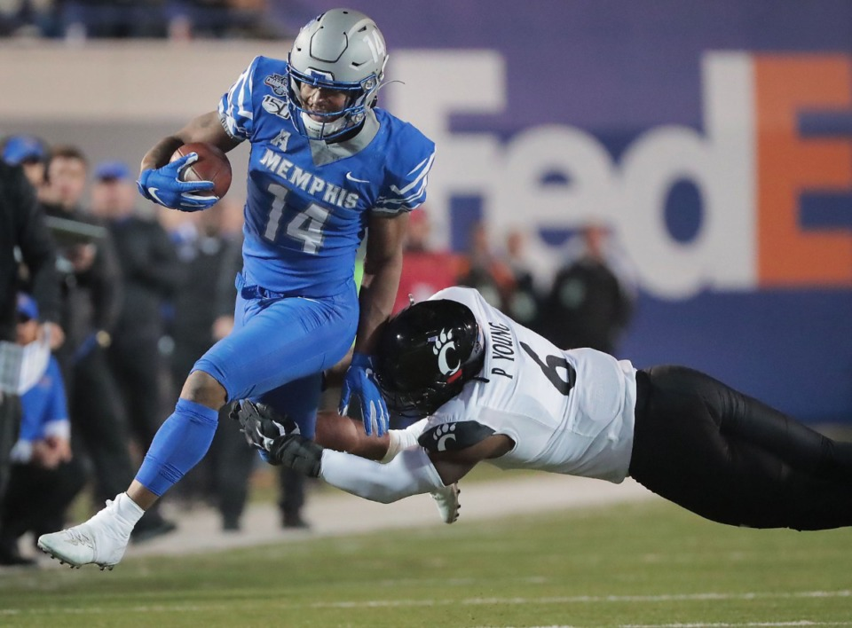 <strong>University of Memphis receiver Antonio Gibson (14) is tackled by Cincinnati's Perry Young during a run in the the Tigers' AAC Championship game on Dec. 7, 2019, against the Bearcats at Liberty Bowl Memorial Stadium.</strong> (Jim Weber/Daily Memphian file)