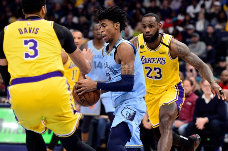 <strong>Memphis Grizzlies guard Ja Morant (12) handles the ball between Los Angeles Lakers forwards LeBron James (23) and Anthony Davis (3) in the first half of an NBA basketball game Saturday, Feb. 29, 2020, in Memphis.</strong> (AP Photo/Brandon Dill)