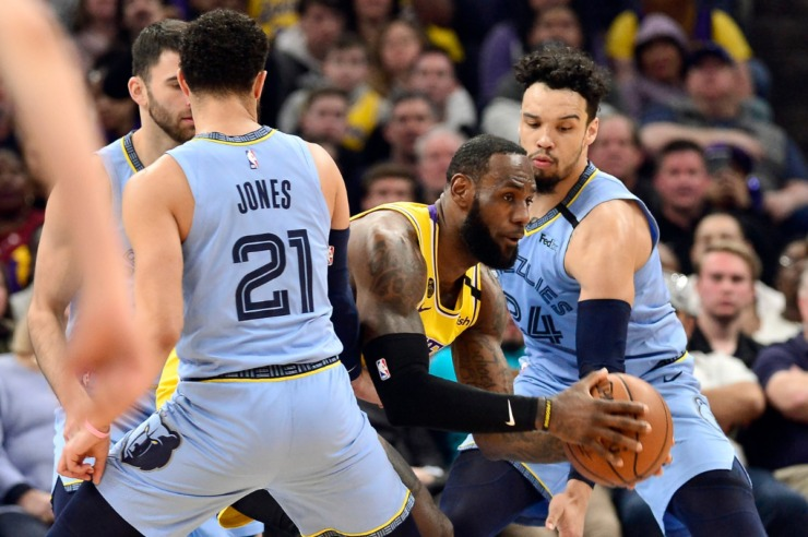 <strong>Los Angeles Lakers forward LeBron James, center, handles the ball between Memphis Grizzlies guards Tyus Jones (21), John Konchar, back left, and Dillon Brooks (24) in the first half of an NBA basketball game Saturday, Feb. 29, 2020, in Memphis.</strong> (AP Photo/Brandon Dill)