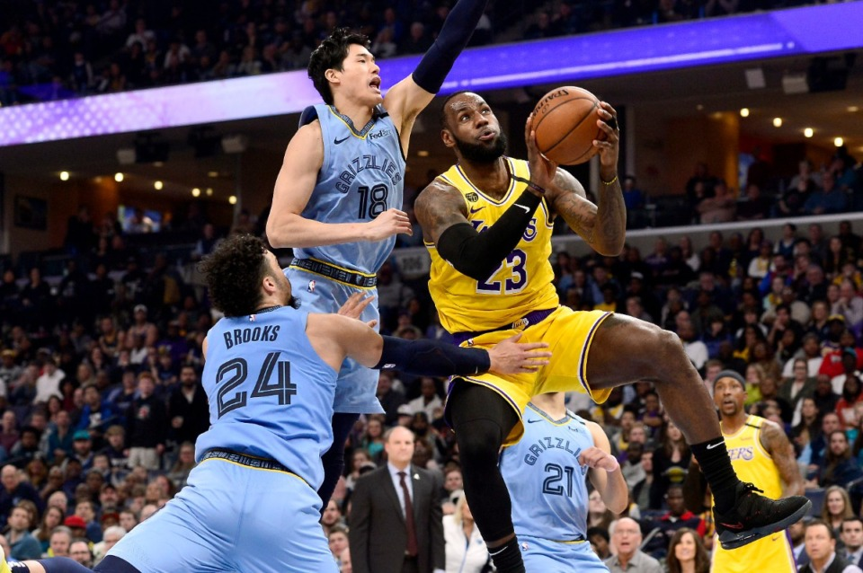 <strong>Los Angeles Lakers forward LeBron James (23) shoots ahead of Memphis Grizzlies guards Yuta Watanabe (18) and Dillon Brooks (24) in the second half of an NBA basketball game Saturday, Feb. 29, 2020, in Memphis.</strong> (AP Photo/Brandon Dill)