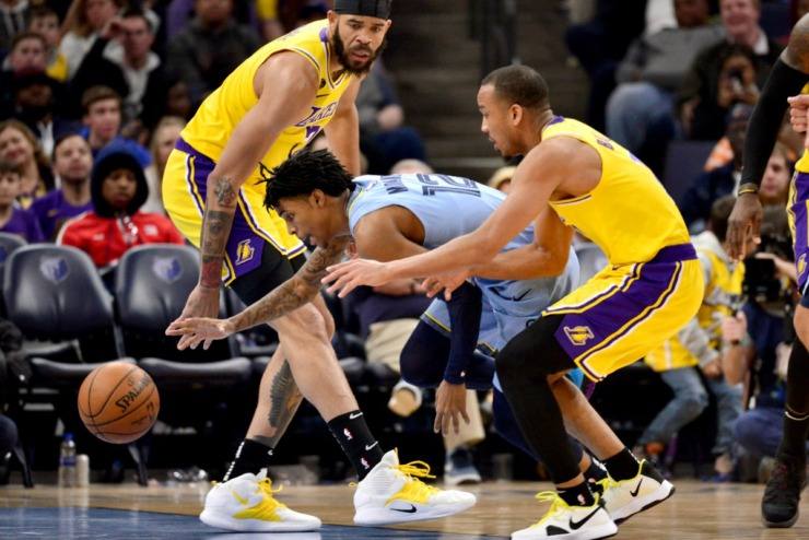 <strong>Memphis Grizzlies guard Ja Morant (12) drives between Los Angeles Lakers center JaVale McGee (7) and guard Avery Bradley, right, in the second half of an NBA basketball game Saturday, Feb. 29, 2020, in Memphis.</strong> (AP Photo/Brandon Dill)