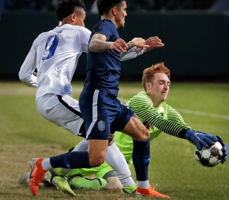 <strong>Tigers goalkeeper Parker Lackland (1) dives for a save as Memphis 901 FC forward Pierre Da Silva (11) closes in for a shot during 901 FC's preseason exhibition game against the University of Memphis at AutoZone Park on Feb. 29, 2020.</strong> (Jim Weber/Daily Memphian)