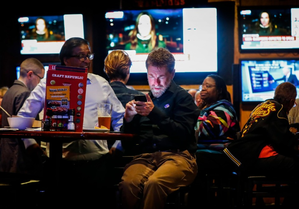 <strong>Houston Wolf (middle) looks at his phone during a Super Tuesday watch party on Tuesday March. 3, 2020, at Craft Republic.</strong> (Mark Weber/Daily Memphian)