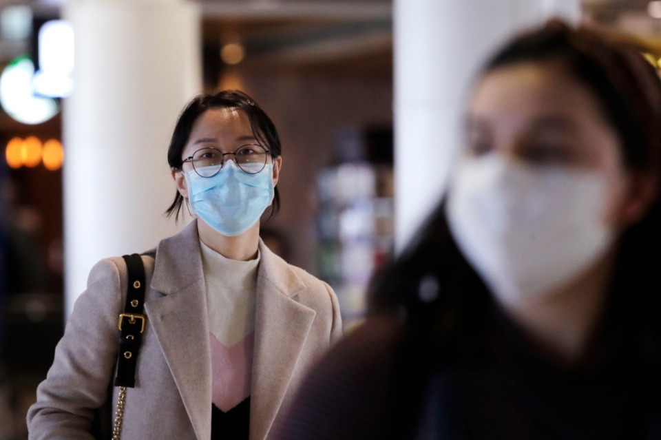 <strong>Travelers at Seattle-Tacoma International Airport wear masks Tuesday, March 3, 2020, in SeaTac, Wash. Six of the 18 Western Washington residents with the coronavirus have died.</strong> (Elaine Thompson/AP)