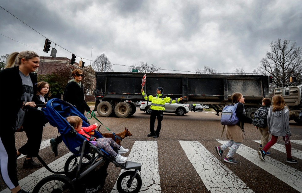 <strong>School Crossing Guard Maggie Jackson (middle) directs traffic for Snowden School parents and students crossing North Parkway on March. 4, 2020. The City Council approved the first of three readings of an ordinance that would bring speed enforcement cameras to school zones..</strong> (Mark Weber/Daily Memphian)