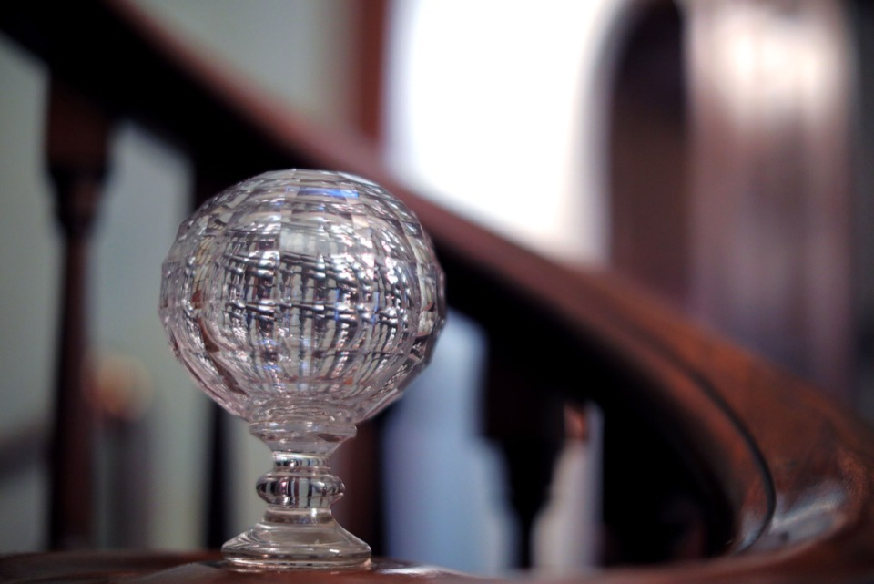 <strong>An ornate crystal ball adorns the bottom of the Annesdale Mansion's winding grand staircase, as seen March 4, 2020.</strong> (Patrick Lantrip/Daily Memphian)